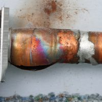 closeup image of a frozen and broken copper radiator pipe