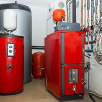 Firewood boiler and puffer tank in the boiler room